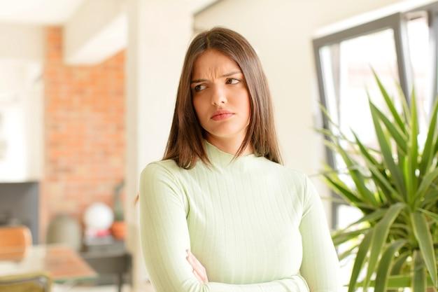 Молодая женщина грустит, расстроена или злится и смотрит в сторону с негативным отношением, хмурясь в знак несогласия Premium Фотографии