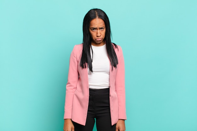 Young woman feeling sad and whiney with an unhappy look, crying with a negative and frustrated attitude