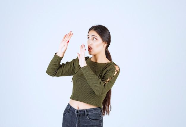 Giovane donna che si sente spaventata e mostra il segnale di stop.
