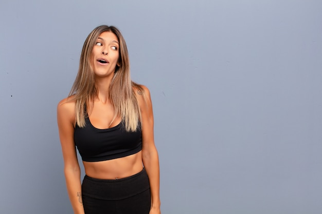Young woman feeling shocked, happy, amazed and surprised, looking to the side with open mouth