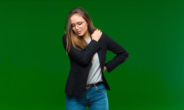 Молодая женщина чувствует усталость, стресс, тревогу, разочарование и депрессию, страдает от боли в спине или шее на зеленом