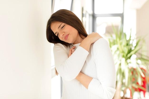 피곤함을 느끼는 젊은 여성은 불안한 좌절감을 강조하고 허리 또는 목 통증으로 고통받습니다.