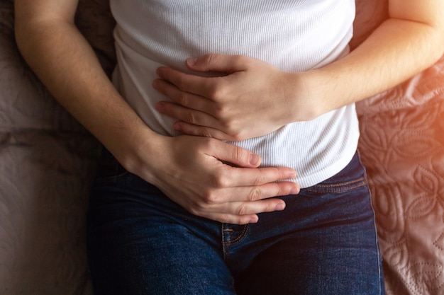 Young woman feels abdominal pain during the period menstruation
