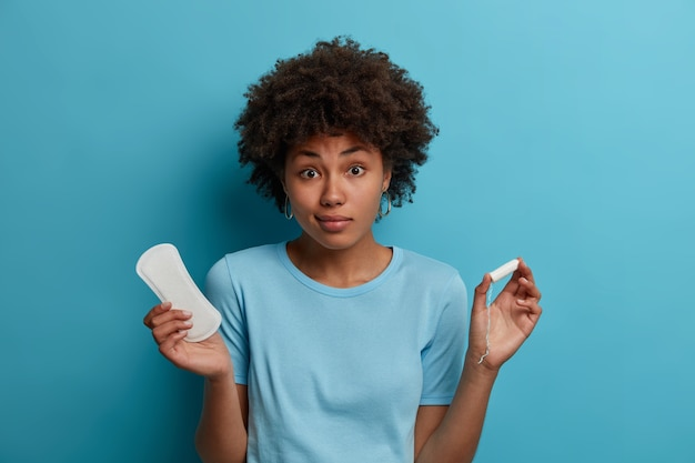 Young woman feels hesitant, chooses between sanitary pad and tampon during critical days, has good hygiene protection, regular menstruation cycle, isolated on blue wall. women and menses
