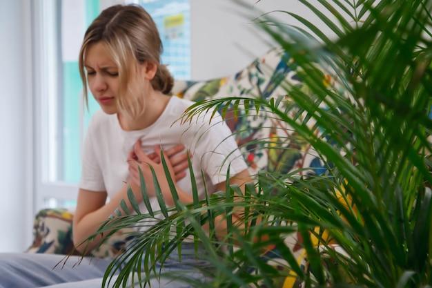 若い女性は彼女の心に痛みを感じています。不健康な女性、ソファに座って胸を抱え、不快感を覚える。健康上の問題、心臓発作、病気の概念。フォアグラウンドでの選択的フォーカス