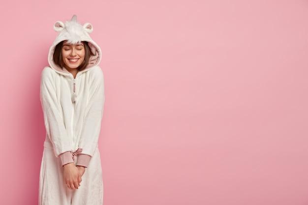 Молодая женщина чувствует удовольствие, наслаждается комфортом в мягком костюме кигуруми, держит руки вместе