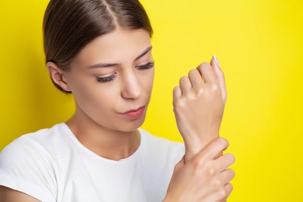 若い女性は彼女の手に激しい痛みを感じます