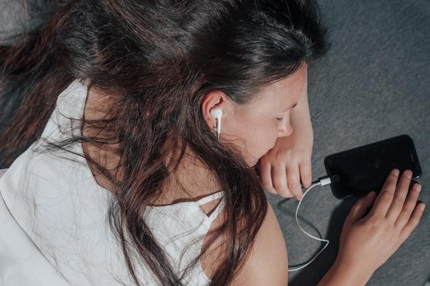 不健康な眠りに落ちる映画を見ながら、若い女性がベッドでスマートフォンで眠りに落ちました