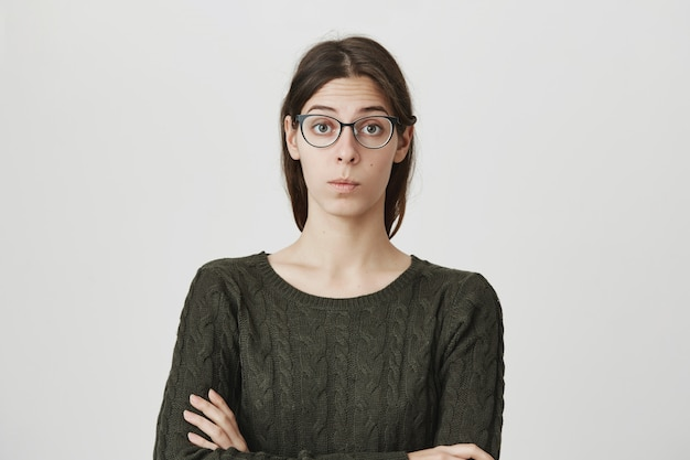 Young woman, female employee in glasses listening coworker with intrigued expression