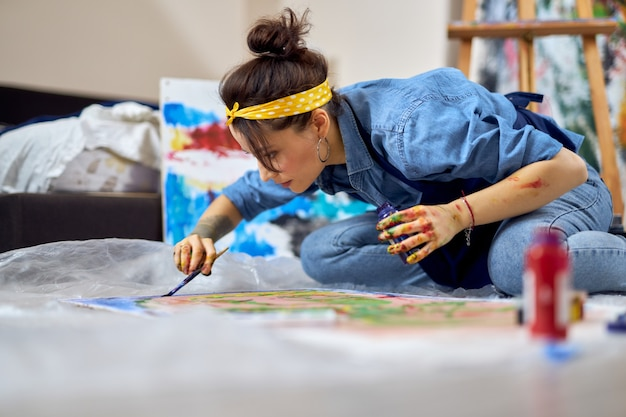 Young woman female painter looking concentrated while working on painting sitting on the floor at