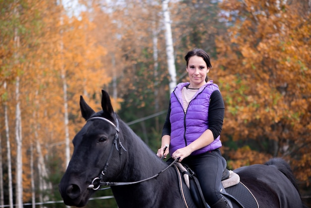 Young woman female riding horse at sunset equitation