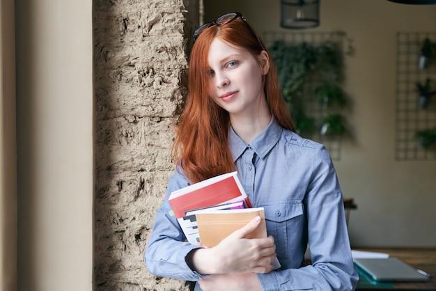 リラックスした自信のある表情で本を手に持つ肖像画にポーズをとって長い赤髪の若い女性女子学生