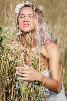 A young woman in a field enjoys the aroma of herbs. smiling blonde in a white dress and a wreath. vertical.