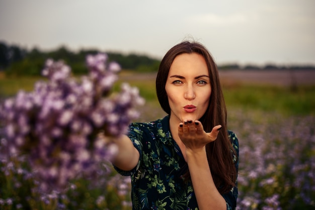 A young woman in the field stretches a bouquet of flowers and sends a kiss to the camera