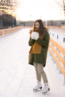 Young woman in figure skates standing on skating rink outdoors in winter day