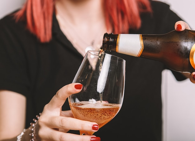 ビールのグラスを埋める若い女性。孤立した画像