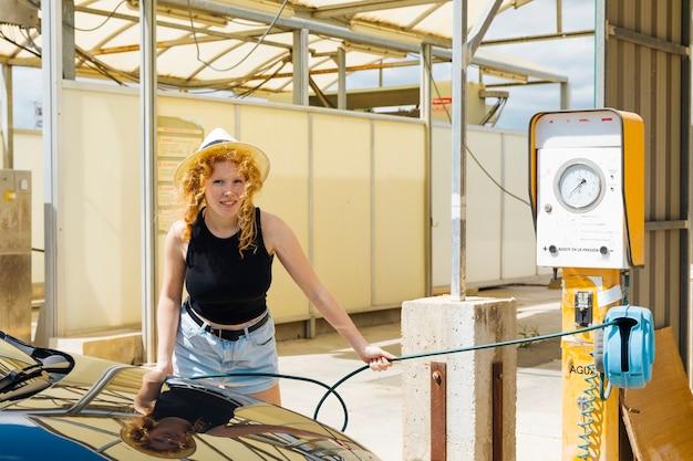 若い女性がガソリンスタンドで空気で自動車のタイヤを充填