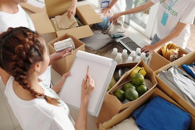 코로나바이러스 전염병으로 실직한 사람들을 위해 자원봉사자 팀이 옷, 음식, 물을 큰 판지 상자에 포장할 때 문서를 작성하는 젊은 여성
