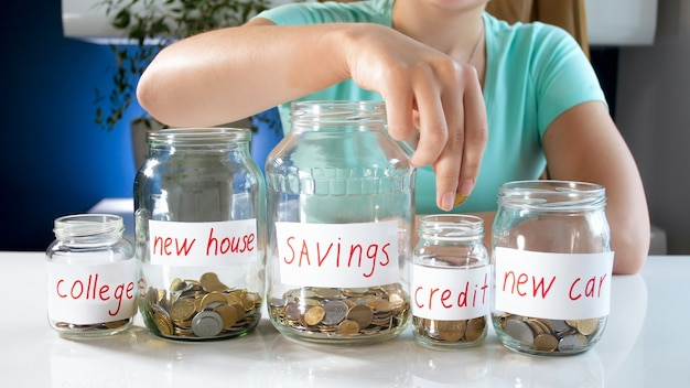 Young woman filling glass jars with money savings. concept of financial investment, economy growth and bank savings.
