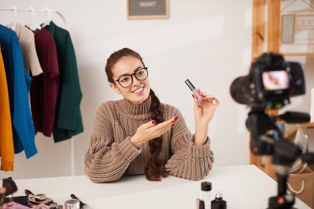 Young woman filming beauty vlog video