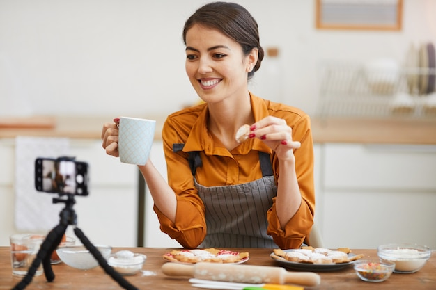 Young woman filming in cozy kitchen