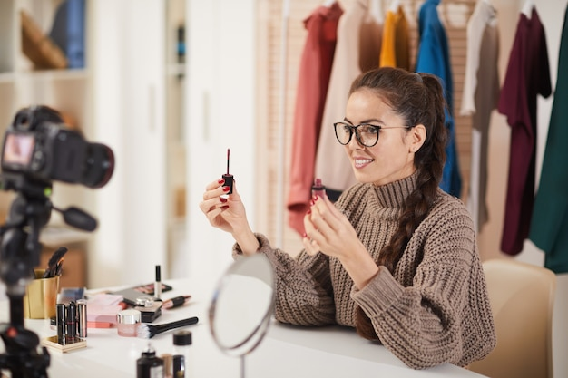 Young woman filming makeup tutorial video