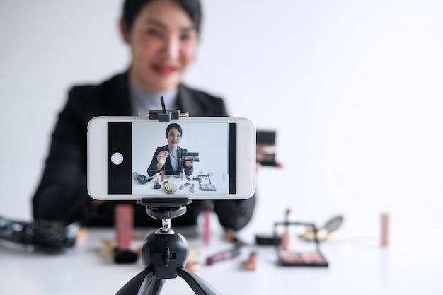 Young woman filming a makeup tutorial