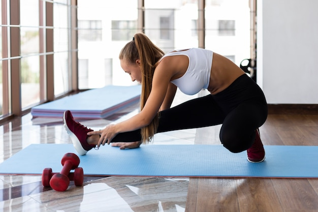 Young woman at fitness class stretching