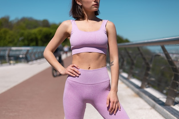 Young woman in fitting sport wear on bridge at hot sunny morning fit showing her abs and figure, sport motivation
