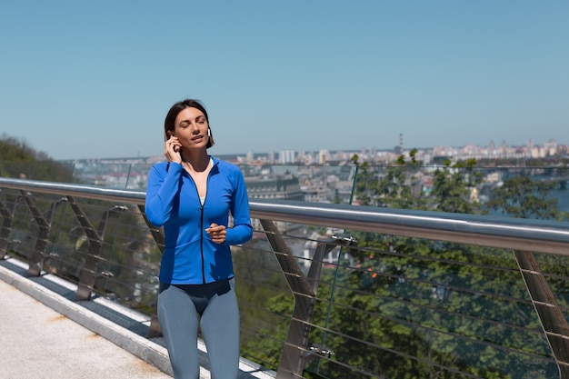 Young woman in fitting sport wear on bridge at hot sunny morning running jogging with headphones happy smile, amazing city view