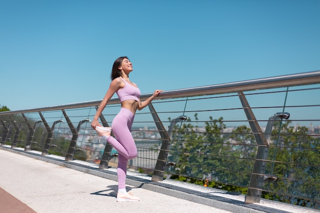 Young woman in fitting sport wear on bridge at hot sunny morning stretch herself
