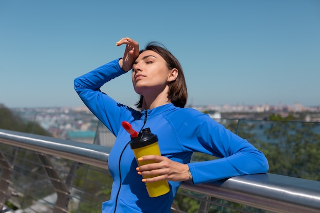 Young woman in fitting sport wear on bridge at hot sunny morning with bottle of water shaker thirsty after workout tired drinking