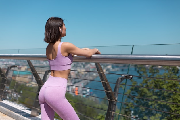 Young woman in fitting sport wear on bridge wireless bluetooth headphones resting after cardio enjoys view and music
