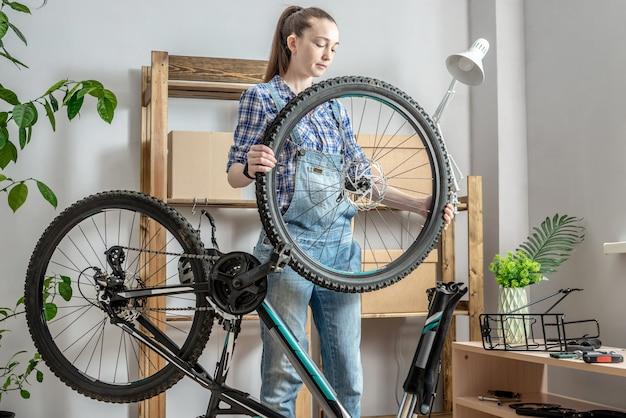 작업장에서 산악 자전거를 고치는 젊은 여성. 새 시즌 준비, 수리 및 유지 보수의 개념
