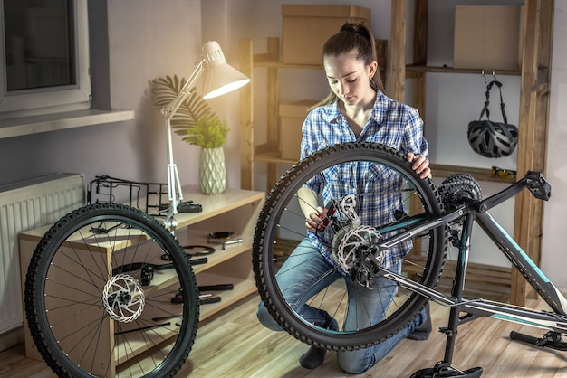 Young woman fixing a mountain bike in a workshop. concept of preparation for the new season, repair and maintenance