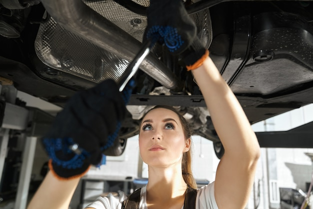 Young woman fixing undercarriage with wrench.