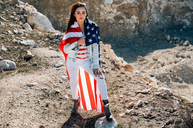 Young woman in flag standing on mountain
