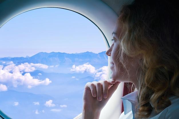 若い女性は、下の山の舷窓を通して見ている飛行機で飛ぶ