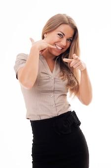 Giovane donna che flirta e che fa il gesto del telefono con la sua mano. ehi, chiamami