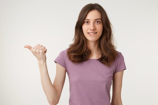 Una giovane donna flirta con un sorriso giocoso si morde il labbro inferiore