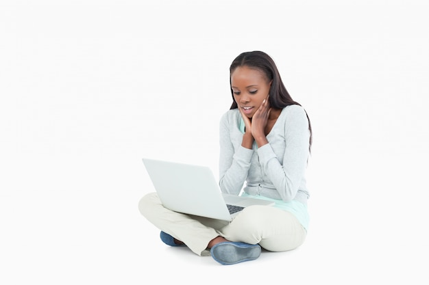 Young woman on the floor seems skeptical about her laptop