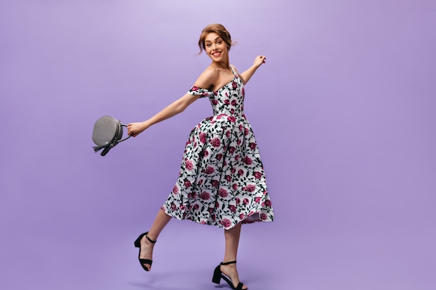 Young woman in floral dress holds handbag and jumps. attractive cute young lady with stylish hairstyle in summer outfit posing.
