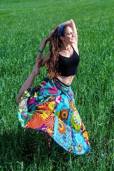 Giovane donna in un vestito floreale che medita nel campo di erba