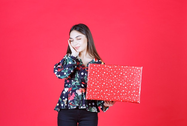 Young woman in floral shirt holding a red gift box with white dots on it and looks confused and thoughtful