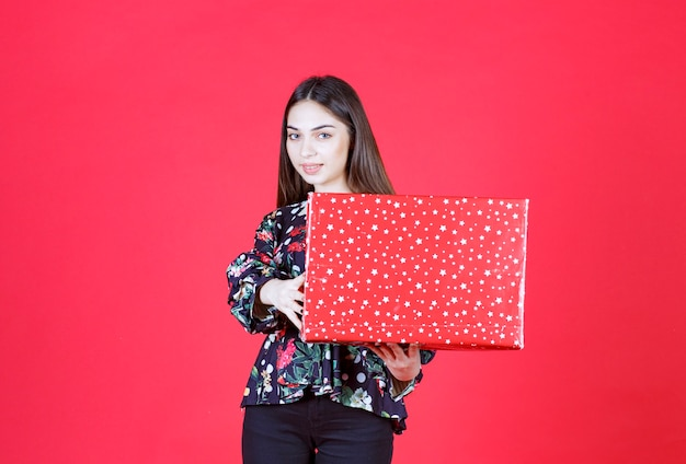 Young woman in floral shirt holding a red gift box with white dots on it