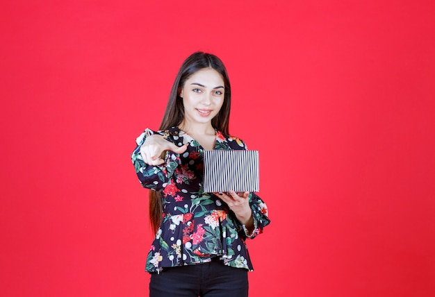 Young woman in floral shirt holding a silver gift box and inviting someone to handle it