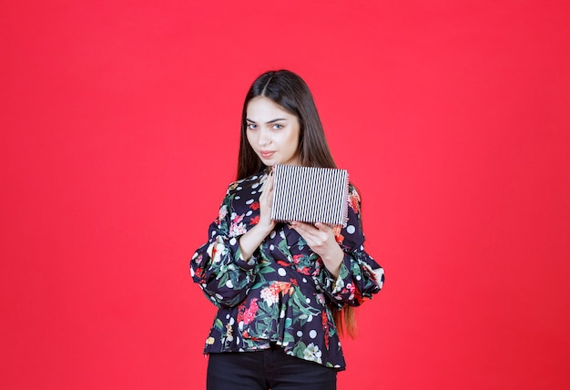 Young woman in floral shirt holding a silver gift box and looks thoughtful
