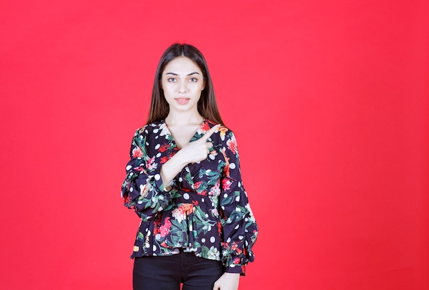 Young woman in floral shirt standing on red wall and pointing to the right