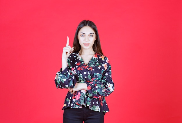 Young woman in floral shirt standing on red wall and showing upside