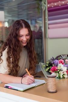 Молодая женщина-флорист принимает заказ на букет цветов в цветочном магазине на рабочем месте